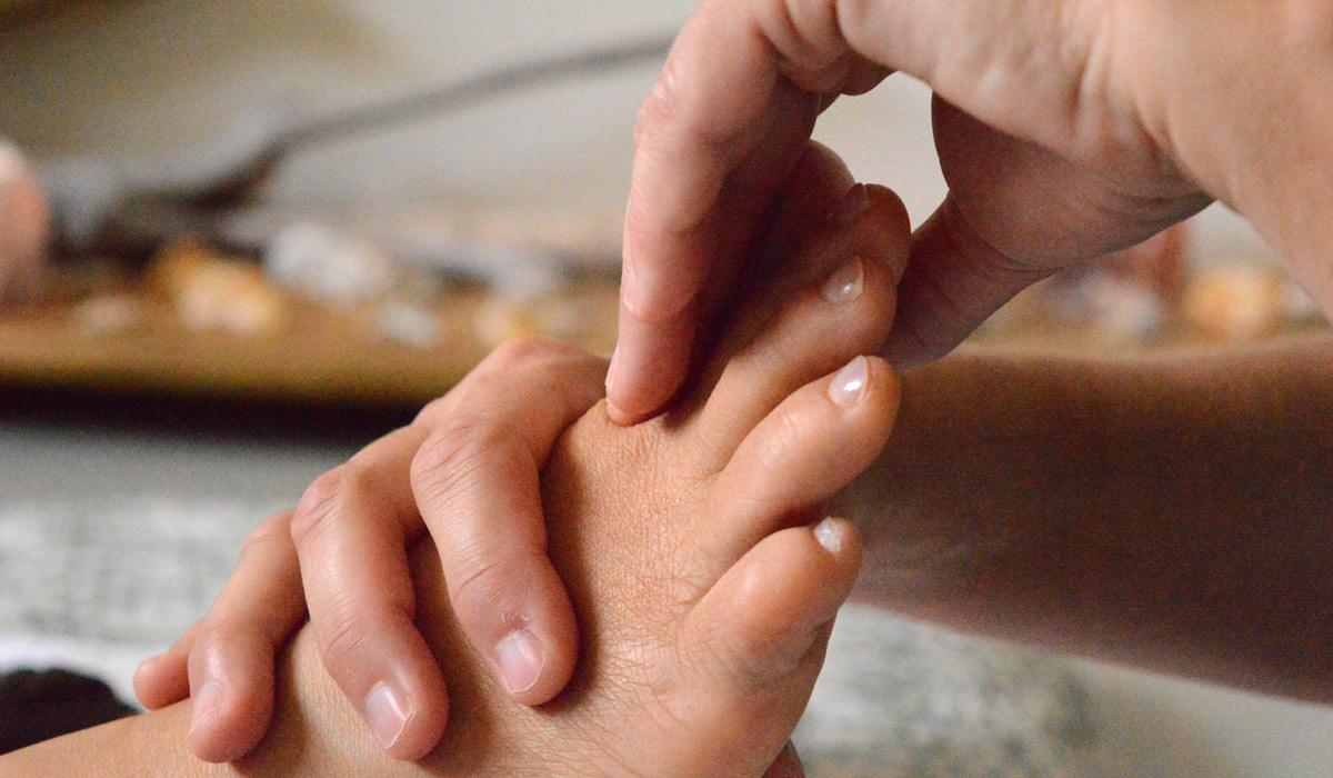 twee handen masseren voet